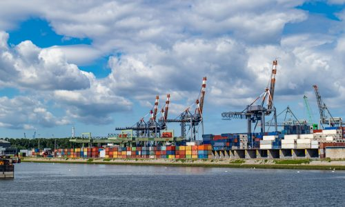Logistics business. International port of Rotterdam Netherlands, Huge cranes, containers and ship, sunny summer day